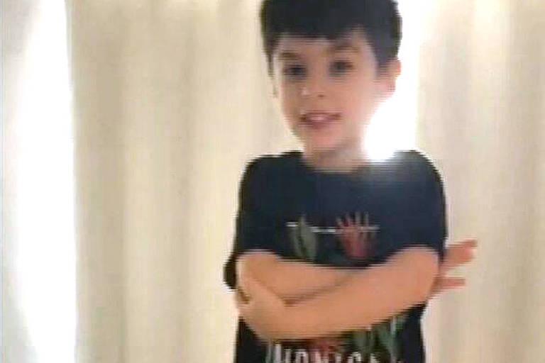 """Menino está em pé, de bermuda escura e camiseta preta com estampa de plantas e a inscrição """"Monica"""" embaixo dos seus braços, que estão cruzados"""