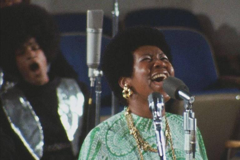Mulher negra usa roupa verde e canta com microfone