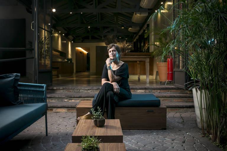 Mulher de roupa preta sentada em banco de madeira
