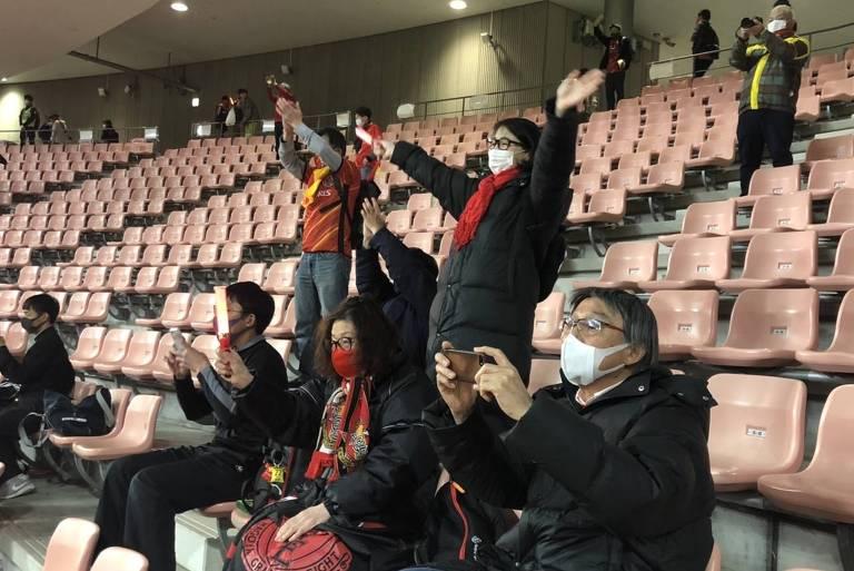 Três pessoas sentadas à frente de duas em pé, com os braços abertos, nas cadeiras do estádio; todas estão de máscara