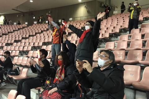 Torcedores do Nagoya comemoram ao fim do jogo; sem gritos, mas com aplausos