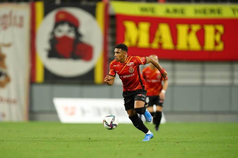 Jogador com uniforme vermelho e preto corre com a bola