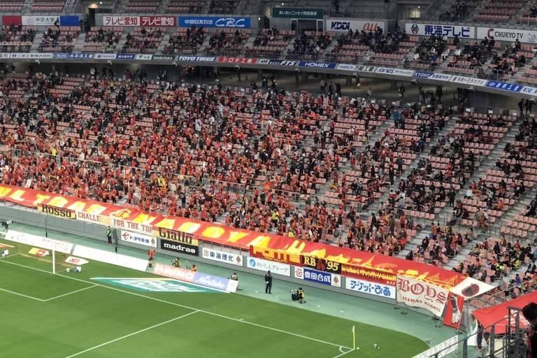 Setor de arquibancada de futebol com presença de torcedores uniformizados