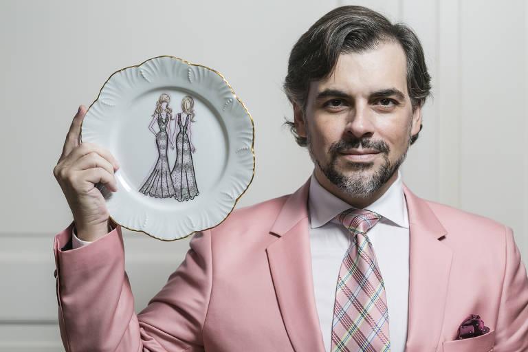 Homem de terno rosa segura prato com desenho