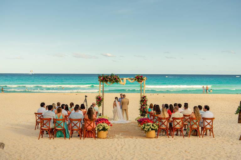 Pessoas em cerimônia de casamento na praia, vistas por trás