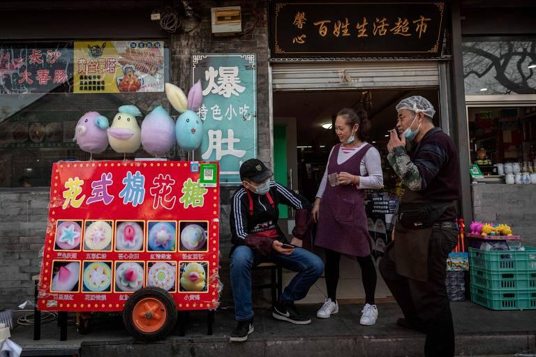 Três pessoas conversam em frente a um restaurante; ao lado esquerdo está uma carrocinha de algodão doce