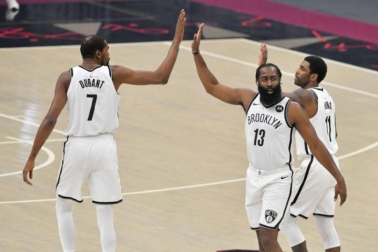 Kevin Durant, James Harden e Kyrie Irving batem as mãos em quadra