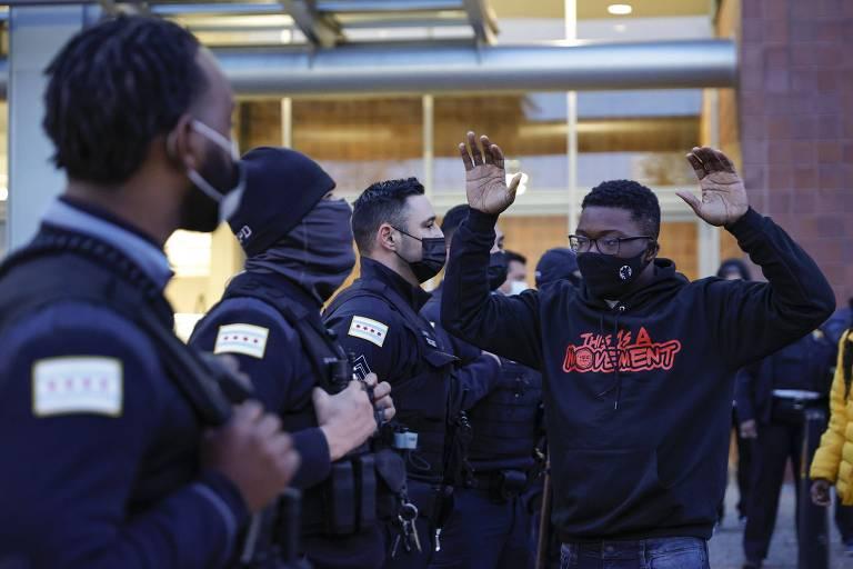 Ativista antirracismo levanta os branços durante manifestação em frente à sede do Departamento de Polícia de Chicago
