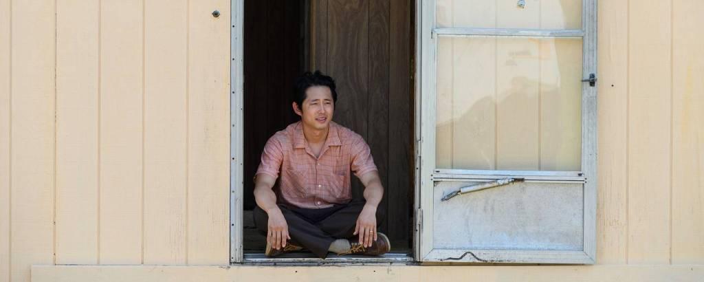 Homem sentado no vão de uma porta aberta