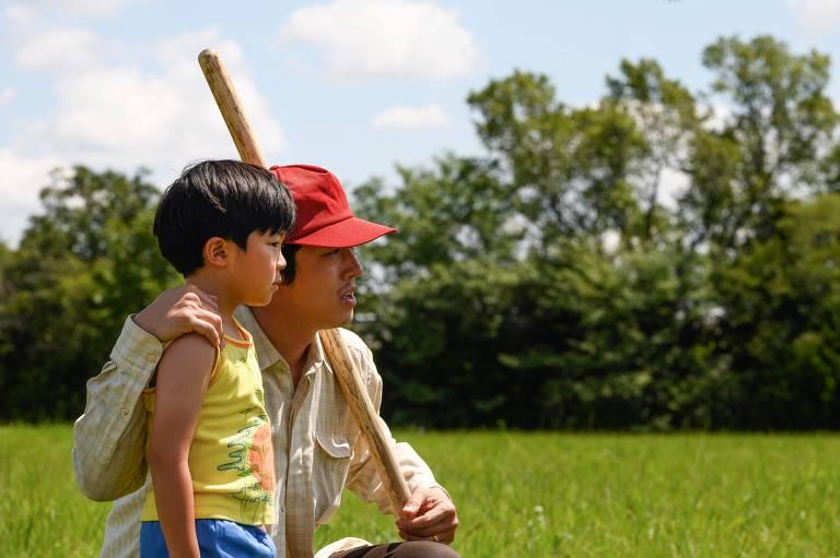 Homem de boné vermelho agachado ao lado de menino em um campo verde