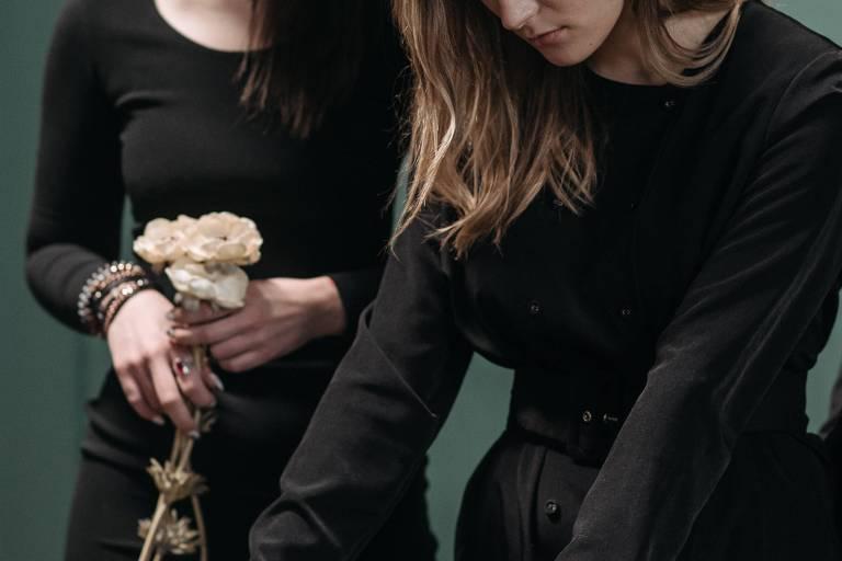 Dupla de mulheres brancas choram em funeral, próximo a um caixão
