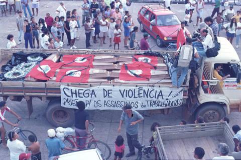 ELDORADO DOS CARAJÁS, PA, BRASIL, 26-04-1996: Caixões com corpos do sem-terra mortos em confronto com polícia militar, em Eldorado dos Carajás (PA). O Massacre de Eldorado dos Carajás foi a morte de dezenove sem-terra que ocorreu em 17 de abril de 1996 no município de Eldorado dos Carajás, no sul do Pará, Brasil decorrente da ação da polícia do estado do Pará. Dezenove sem-terra foram mortos pela Polícia Militar do Estado do Pará. O confronto ocorreu quando 1.500 sem-terra que estavam acampados na região decidiram fazer uma marcha em protesto contra a demora da desapropriação de terras, principalmente as da Fazenda Macaxeira. A Polícia Militar foi encarregada de tirá-los do local, porque estariam obstruindo a rodovia BR-155, que liga a capital do estado Belém ao sul do estado. (Foto: Jorge Araújo/Folhapress)
