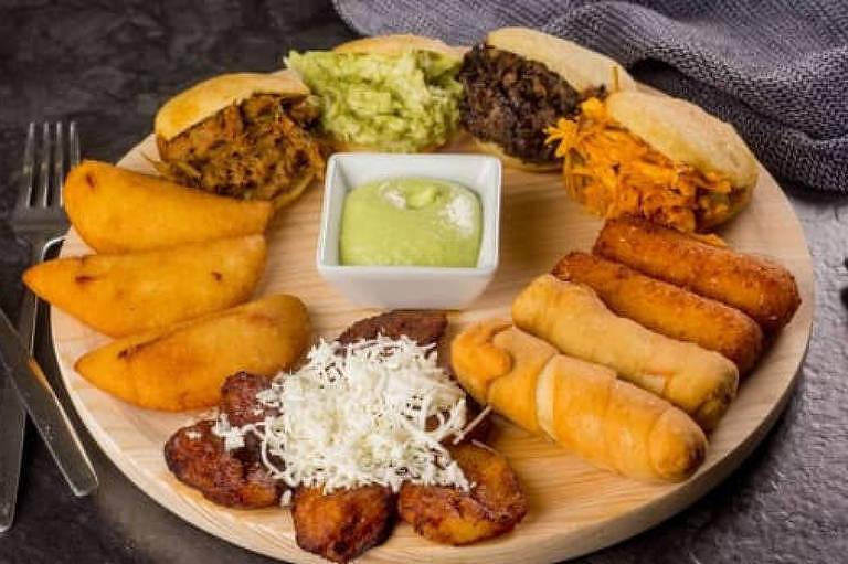 Prato com diferentes quitutes venezuelanos como arepas recheadas, empanadas e dedinhos de queijo