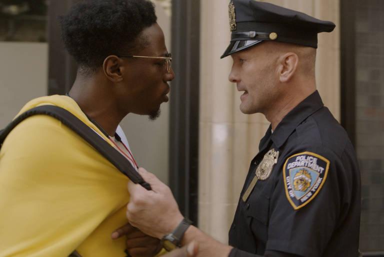 um policial branco traz para si um homem negro pelas alças da mochila dele