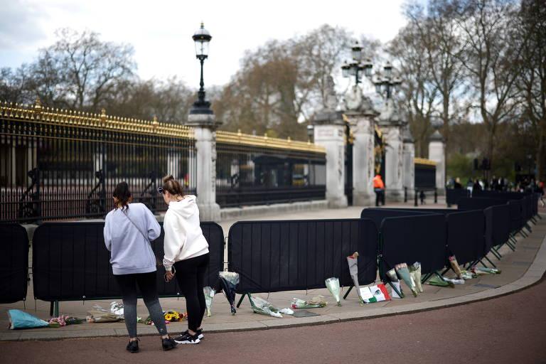 Britânicas observam flores deixadas em homenagem ao príncipe Philip em frente ao Palácio de Buckingham, em Londres