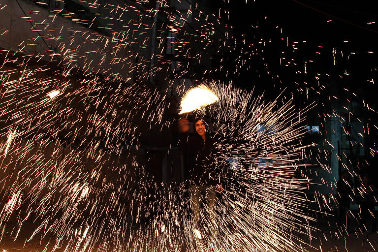 Imagem mostra homem envolto em faíscas de luz brancas, provindas de fogos artificiais de um bastão em sua mão