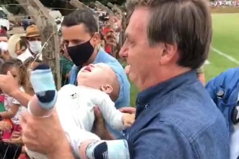 O presidente Jair Bolsonaro segua um bebê, que chora, ao cumprimentar apoiadores em Goianápolis