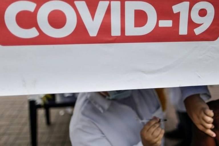 """homem é vacinado por enfermeira embaixo de placa branca com letreiro vermelho """"covid-19"""""""