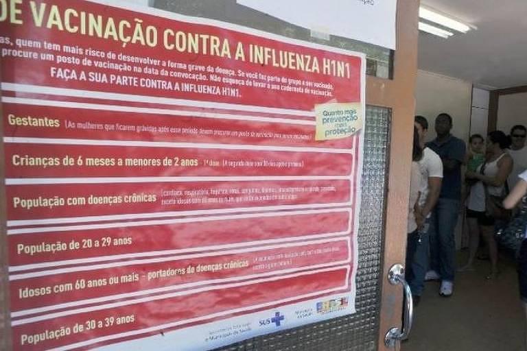 placa vermelha com letreiro amarelo dá orientações sobre vacinação