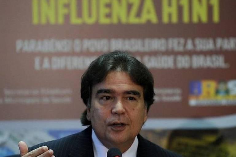 """homem veste terno e gesticula, discursando; ao fundo, uma placa marrom com letreiro amarelo diz """"influenza h1n1"""""""