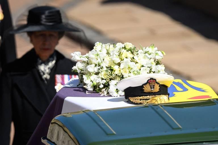 mulher veste roupas pretas e caminha atrás de caixão revestido por bandeira e flores