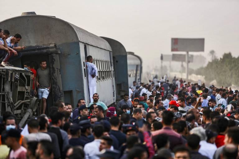 Pessoas próximas a vagões de trem que descarrilhou na cidade de Toukh, na provínica de Caliubia, no Egito