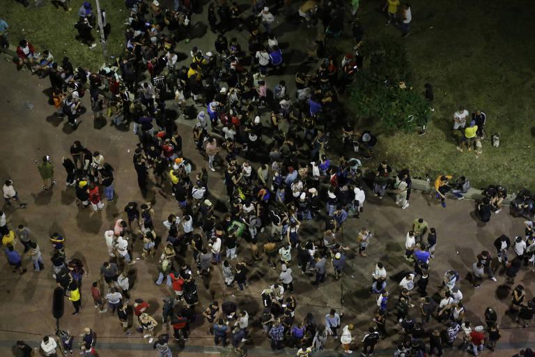 Multidão com dezenas de pessoas é vista de cima sobre calçada e gramado
