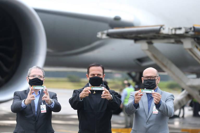 Jean Carlo Gorinchteyn, João Doria e Dimas Covas; eles seguram uma caixinha com os braços estendidos. Ao fundo, um avião