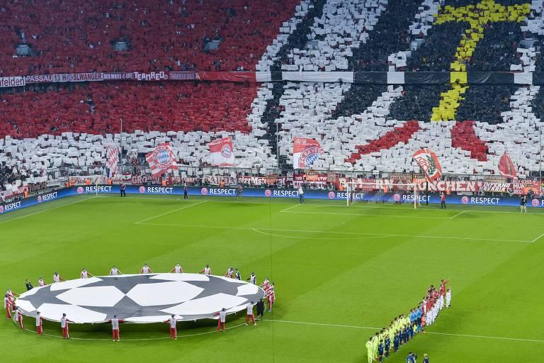 Bandeira com a bola que simboliza o torneio no centro do gramado e times perfilados em estádio cheio