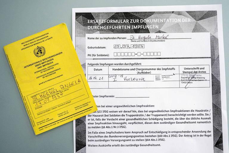 Papel pequeno amarelo onde está escrito o nome de Angela Merkel e folha maior certificando a vacinação