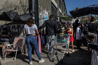 People stand in line for a COVID-19 test on April 12, 2021, in the neighborhood where Carla Huanca lives in the southern reaches of Buenos Aires.