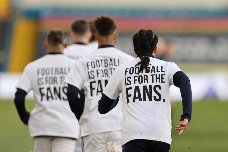 """Jogadores do Leeds United aquecem com camisetas que dizem """"futebol é para os torcedores"""" antes do jogo contra o Liverpool, pela Premier League"""