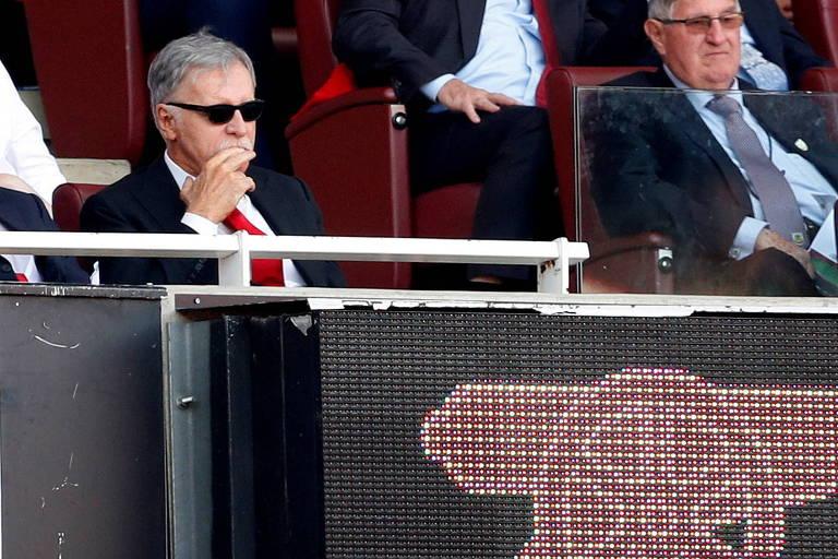 Homem de terno e óculos escuro sentado com a mão na boca em estádio de futebol