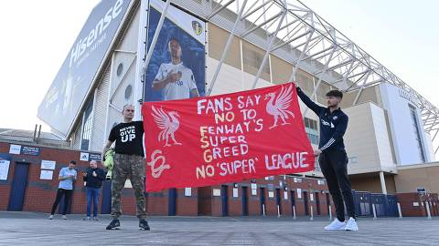 Leeds United fans hold a banner against plans for a European Super League and the involvement of Liverpool football club outside Elland Road ahead of the English Premier League football match between Leeds United and Liverpool in Leeds, northern England, on April 19, 2021. - Twelve of Europe's biggest clubs on Monday said they planned to launch a breakaway Super League, despite the threat of an international ban for them and their players.