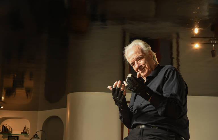 O maestro é visto da cintura para cima; ele veste roupa preta e está olhando para as duas mãos, que estão levantadas na altura do pescoço