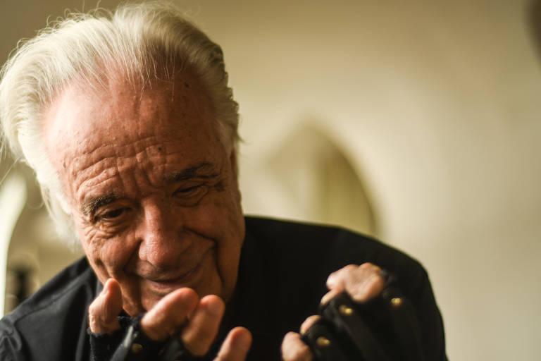 João Carlos Martins retratado do peito para cima, de camisa preta, olha para suas mãos; os dedos com uma luva preta que vai até a metade dos dedos aparecem em primeiro plano