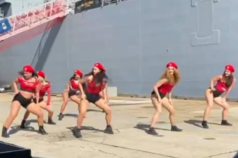 O grupo dançando twerk em frente ao novo navio de guerra australiano HMAS Supply