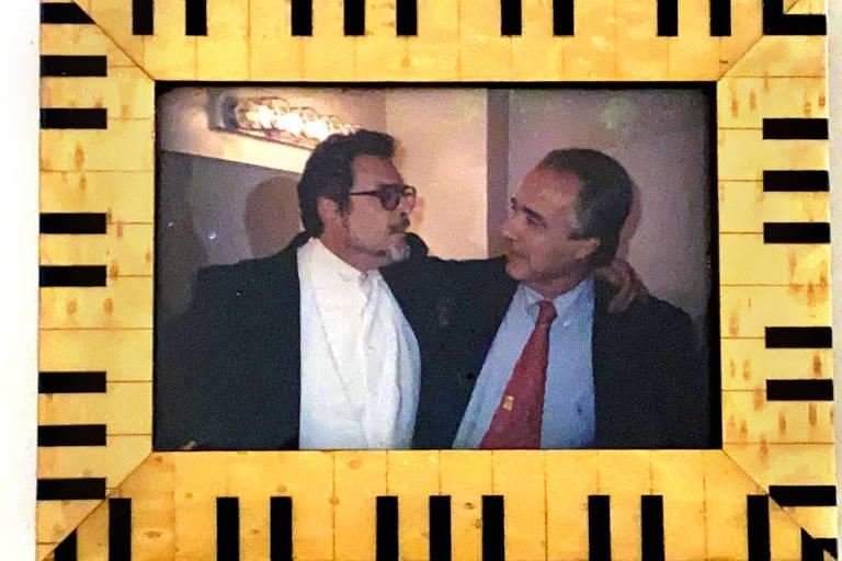 Foto de uma foto em um porta-retrato com moldura que imita um piano. Na foto, os músicos Leon Fleisher e João Carlos Martins estão de lado, abraçados, um olhando para o outro