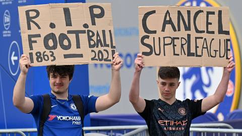 Supporters hold up placards critical of the idea of a New European Super League, outside English Premier League club Chelsea's Stamford Bridge stadium in London on April 20, 2021, ahead of their game against Brighton. - The 14 Premier League clubs not involved in the proposed European Super League