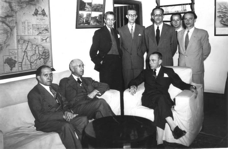 Oito homens brancos de terno e gravata numa sala de visitas. Dois estão juntos em um sofá e outro numa poltrona ao lado. Os outros cinco estão em pé, atrás deles. Há vários quadros nas paredes e uma mesa de centro à frente do sofá e da poltrona.