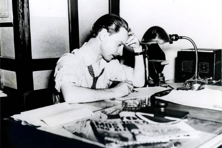 homem sentado escrevendo com caneta em um papel, ele apoia a cabeça em uma das mãos e parece muito concentrado