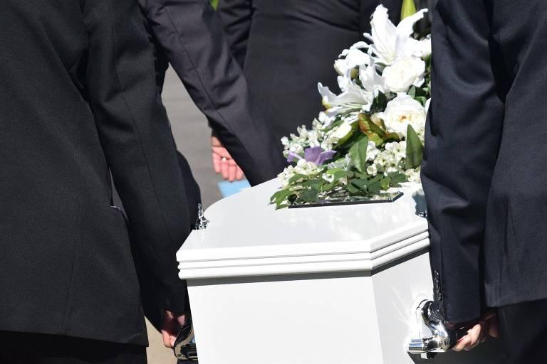 Homens de terno preto carregam caixão branco, com flores brancas