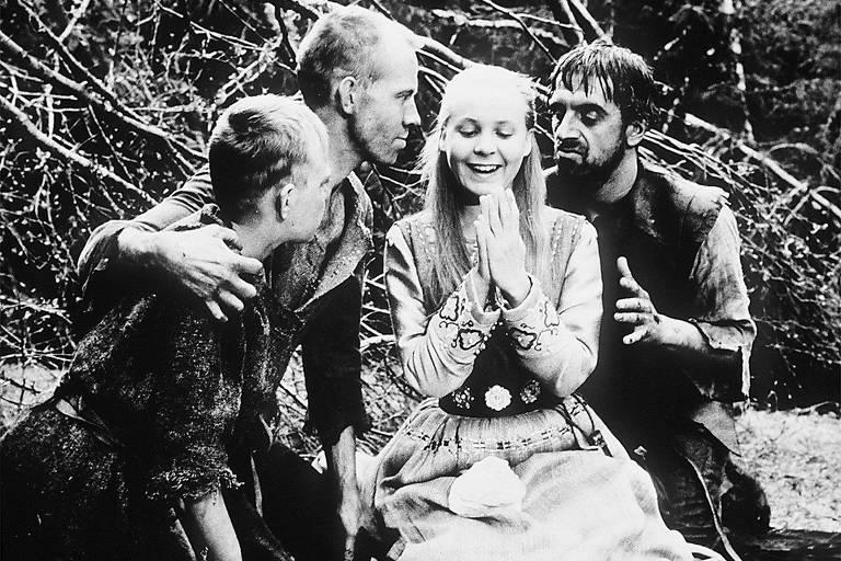 Quatro homens cercam uma mulher loira que sorri enquanto eles os olham maliciosamente