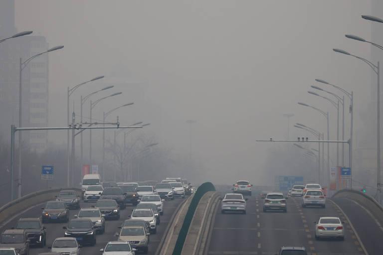 Carros se deslocam em Pequim, em dia de forte acúmulo de poluição no ar