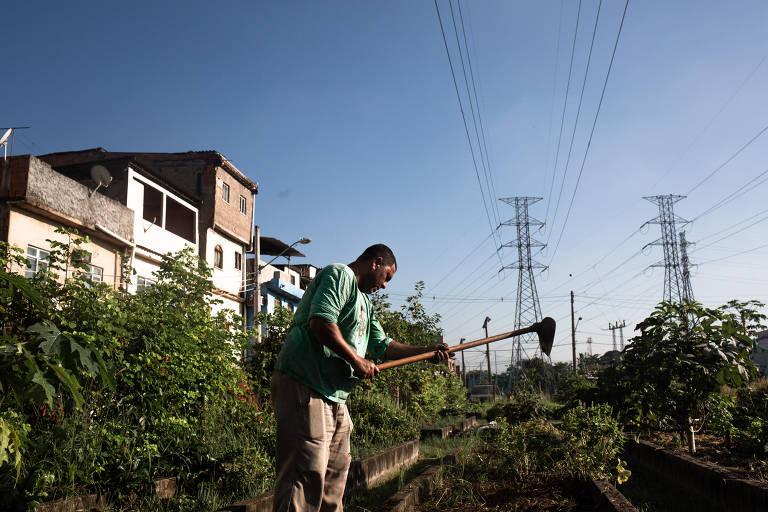 Ezequiel segura uma enxada; ele está trabalhando a terra da horta