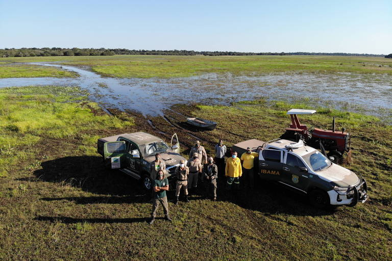 Homens com carros em meio a área de vegetação do pantanal