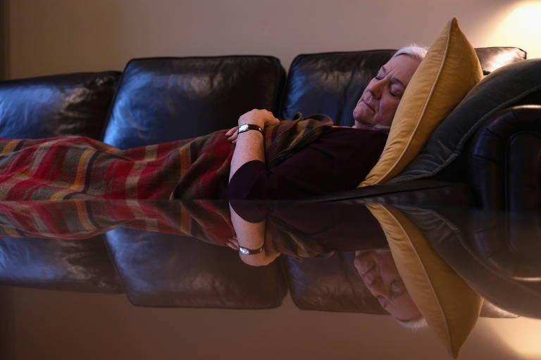 Mulher mais velha deitada em sofá, dormindo