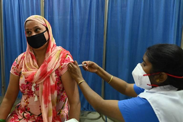 Uma mulher recebe dose da vacina Covaxin, produzida pela empresa Bharat Biotech, em Nova Déli, na Índia