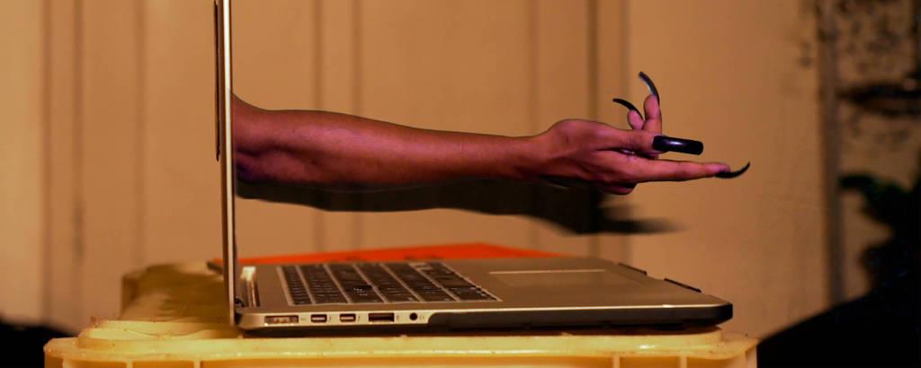 Imagem mostra lateral de notebook; da tela, sai uma mão com unhas longas, que aponta para frente