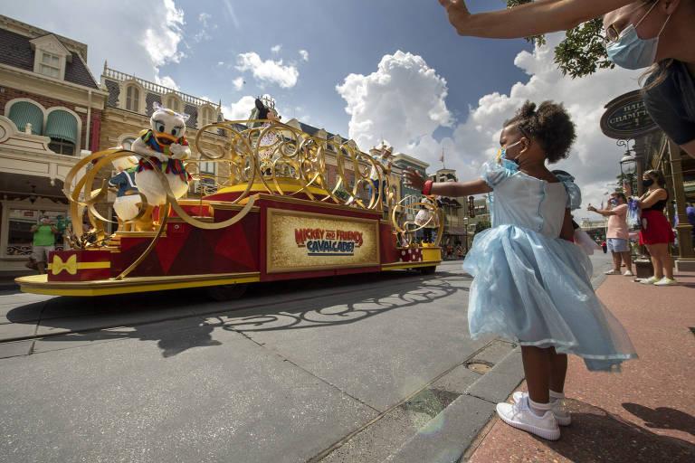 Menina pequena vestida de Cinderela acena para personagem em caravana